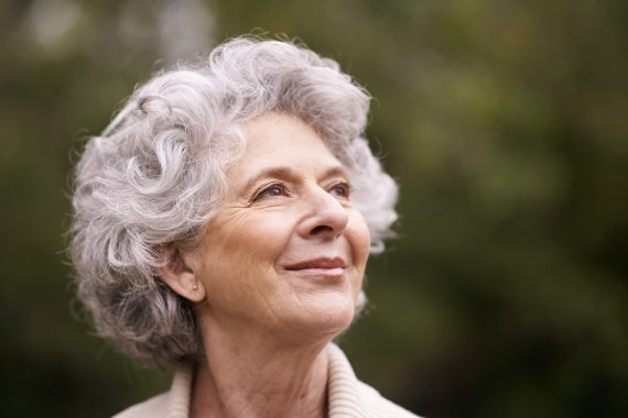 Woman with grey hair smiling confidently.