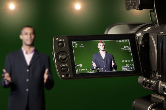 Man in blazer jacket standing in front of a video camera