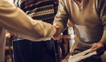 Handshake between business man and older couple