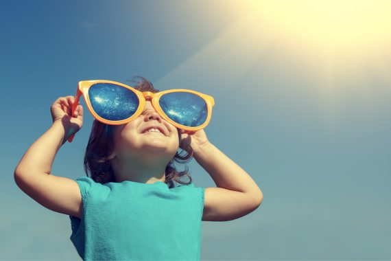 Child looking through oversized plastic glasses toward the sun