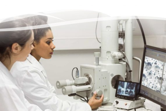 two research scientists looking at a microscopic computer