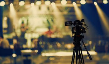 Video camera on tripod recording stage