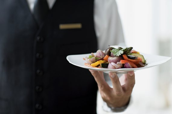 Table waiting staff with a plate of cold salad.