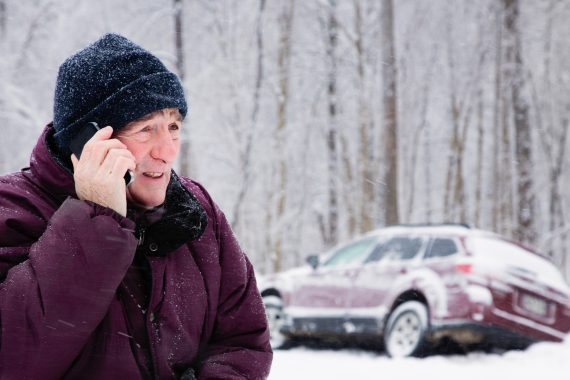 man on cellphone in snowstorm with car in snow bank on the side of the road