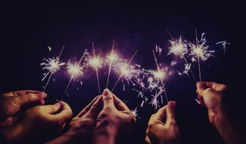 Many hands holding hand-held fireworks