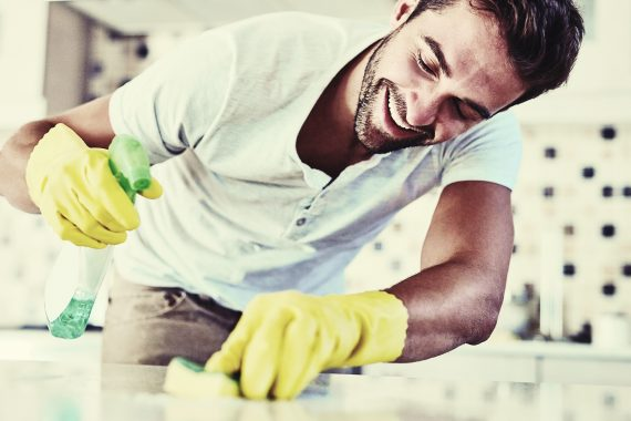 Man cleaning counter with spray bottle and sponge wearing yellow gloves