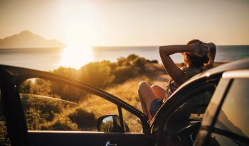 Person watching the sunset while reclining on the hood of their car with the door open