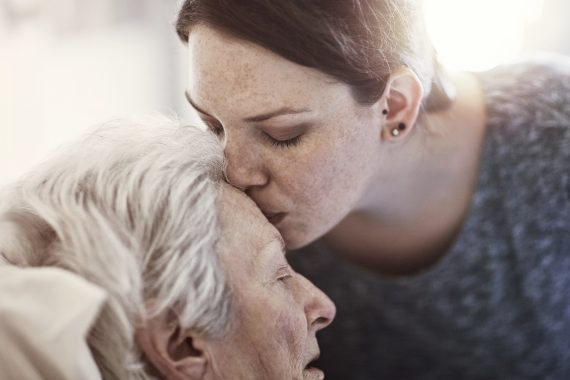 Woman kissing older woman's forehead