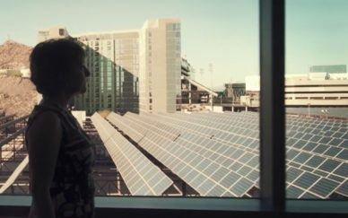 Woman looking out the window at solar panels
