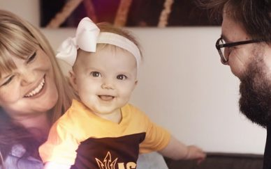 Happy family with small child wearing ASU colors