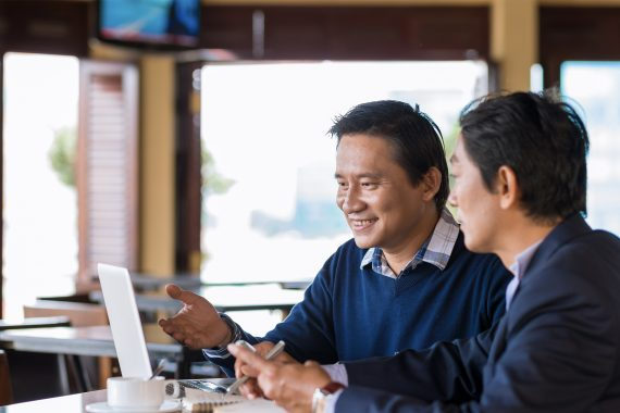 Business meeting with two happy people at a cafe table with computer.