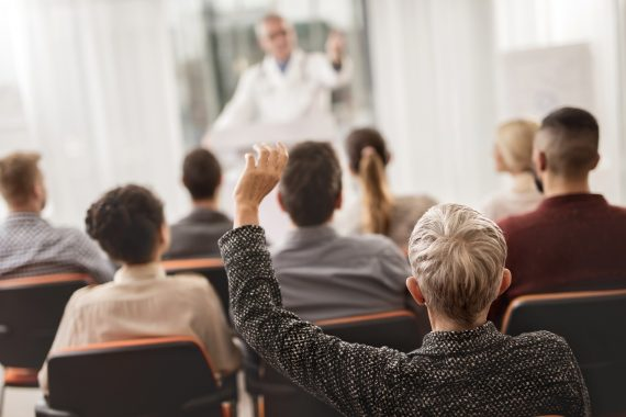 Person raising their hand in the audience of a medical professional presentation.